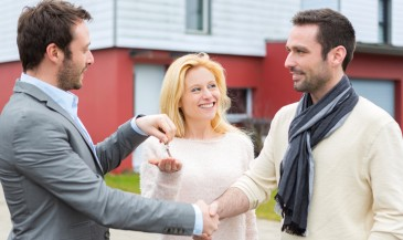 Property agent handing keys to new home to couple, while shaking man's hand